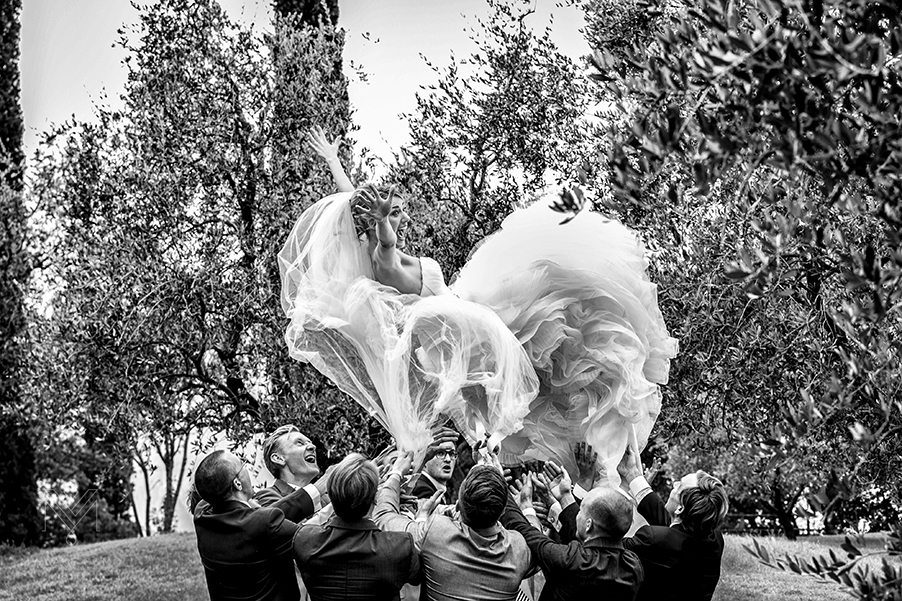 A-bride-being-thrown-by-the-groomsmen-at-Lake-Como-wedding