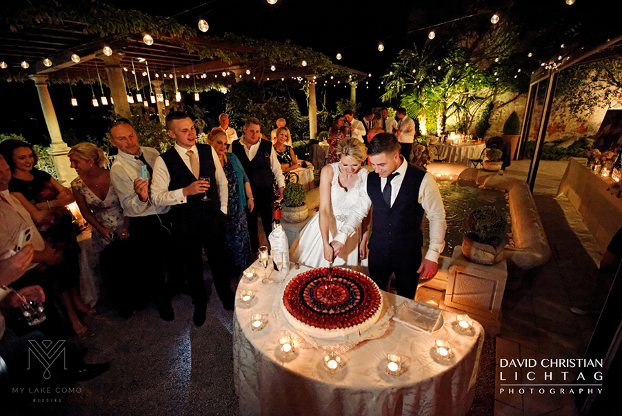 Wedding-cake-cutting-on-the-outdoor-alfresco-dining-terrace-at-Villa-Cipressi