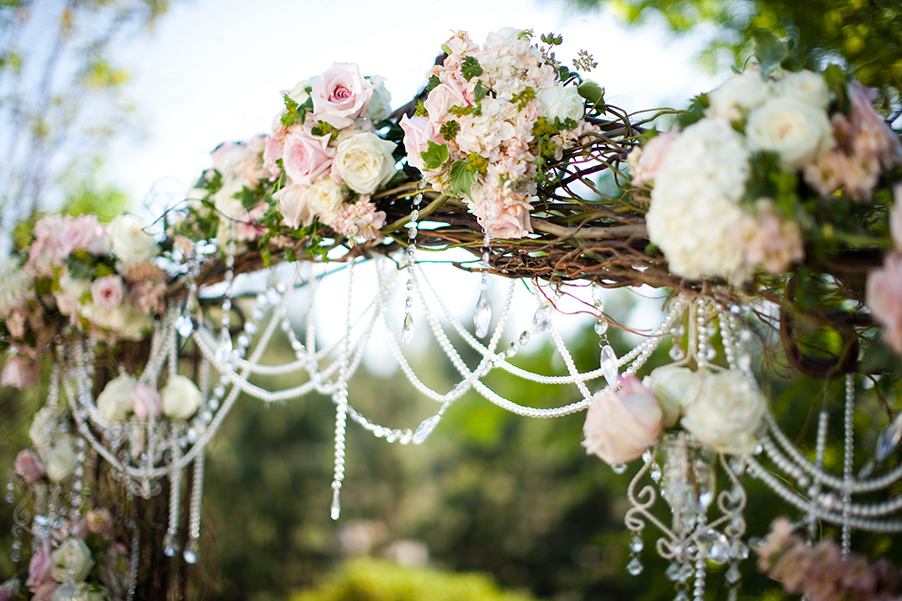 Rose-wedding-ceremony-arch-with-pink-coral-white-and-ivory-flowers-and-pearl-crystal-garlands