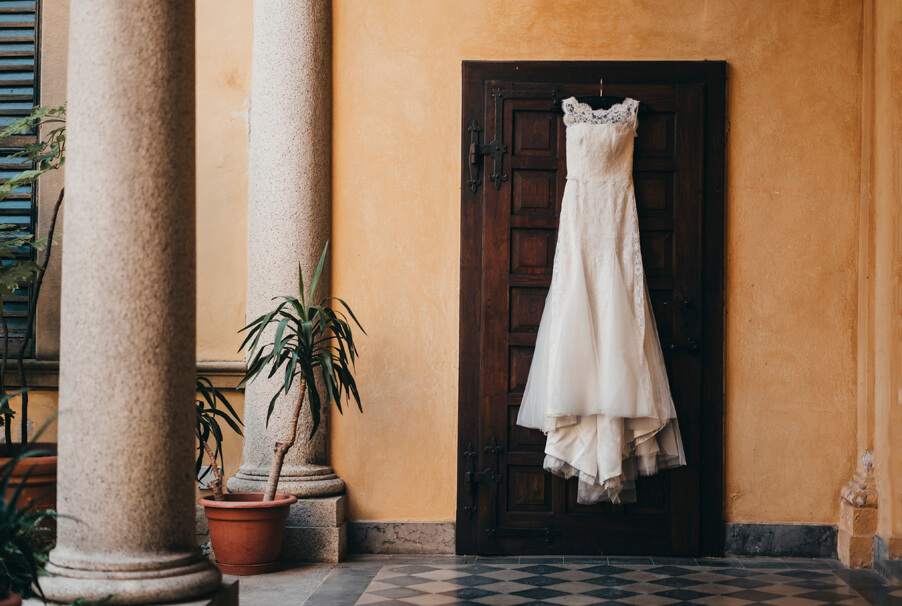 Wedding-dress-hanging-in-rustic-Italian-courtyard-with-columns
