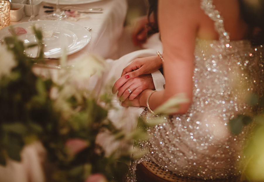 Bride-and-groom-hold-hands-at-their-sweet-heart-table-at-Villa-Pizzo
