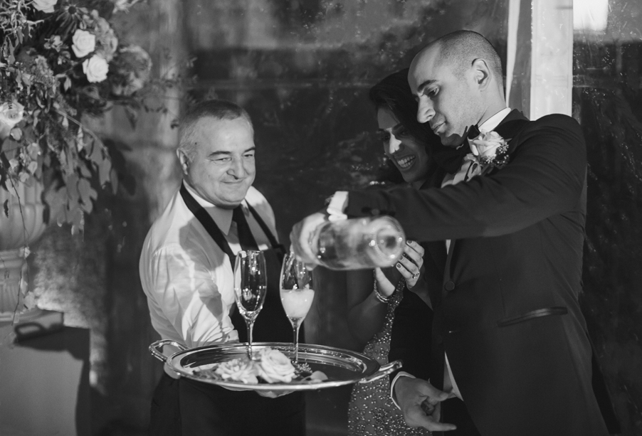 Bride-and-groom-pour-Champagne-on-their-wedding-day-at-Villa-Pizzo-Lake-Como