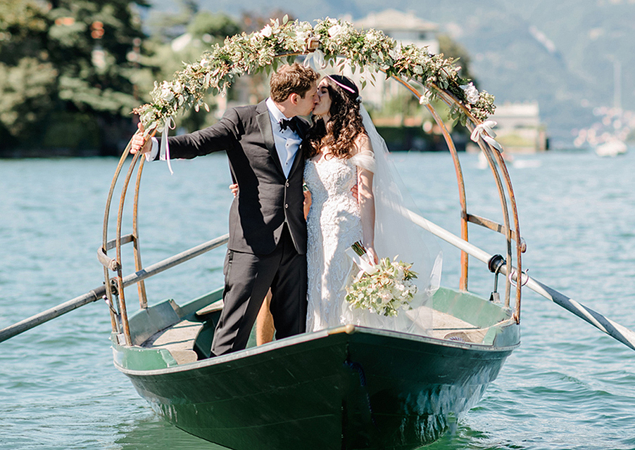 Bride-and-groom-on-Lucia-row-boat-on-Lake-Como-in-Italy-for-wedding-day
