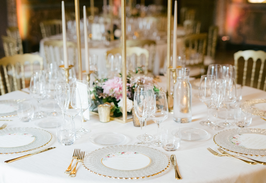 Wedding-dinner-setting-with-gold-cutlery-and-clear-under-plates